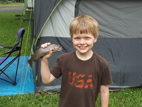 kid smiling while holding caught fish