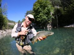 Fly fisherman holding fario trout