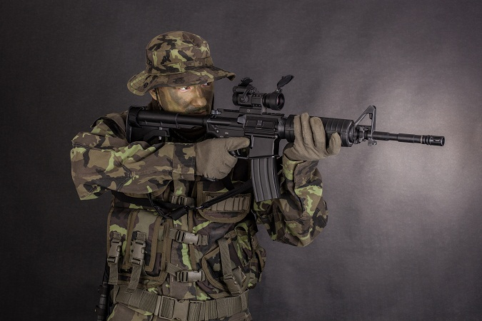 man in camouflage holding M4 carbine