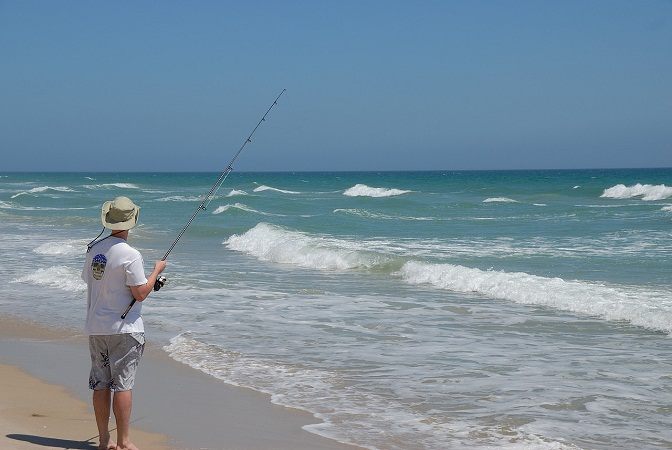 man surf fishing