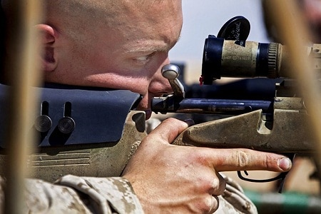 man looking through rifle scope