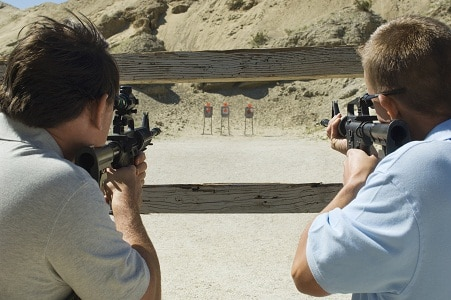 two men aiming rifles at firing range