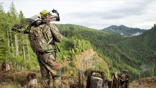 hunter carrying backpack and bow
