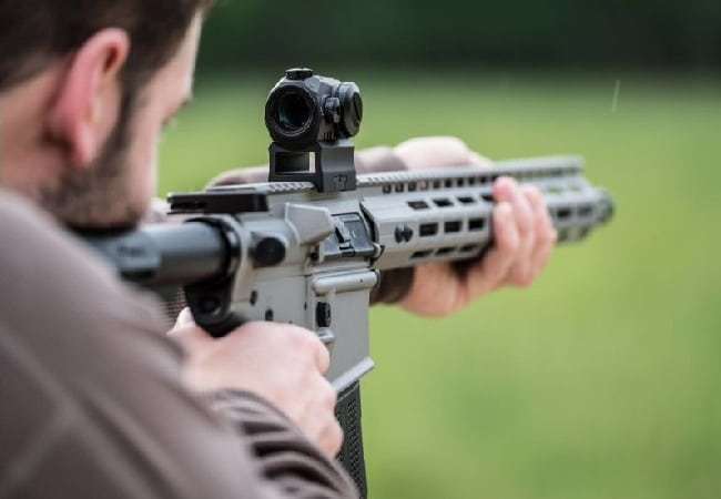 A person aiming through the best ar-15 red dot