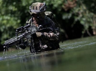 soldier standing in water with red dot scope on gun