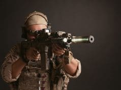 man in full gear aiming airsoft rifle using holographic sight