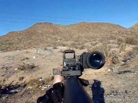 rifle held in open field with magnifier flipped to side