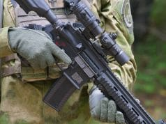 uniformed man holding airsoft rifle with sights