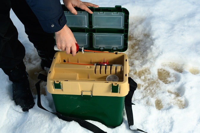 fisher holding tackle box on snow