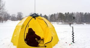 fisher in a yellow tent on snow