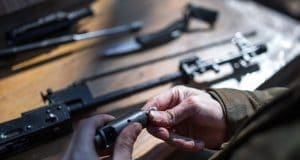 man hands cleaning rifle parts on table